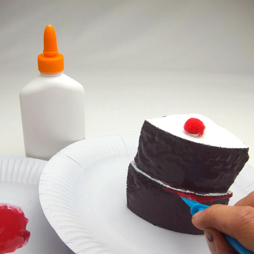 Finishing touches to play food cake slice.